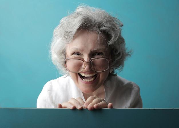 Vieille dame aux cheveux blancs avec des lunettes et un large sourire derrière un mur turquoise