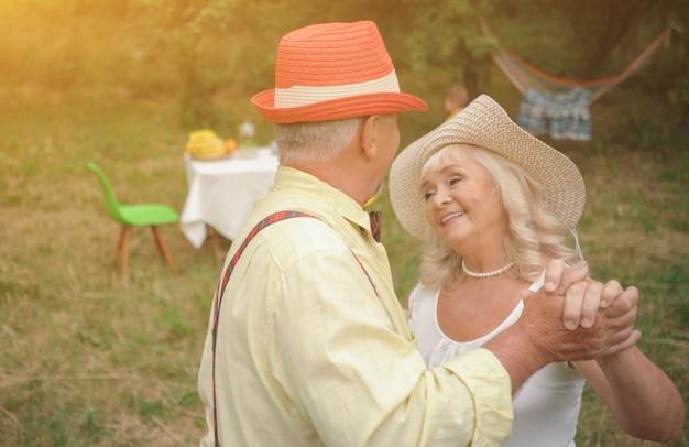 La vieille dame et gentleman dansant dans le jardin