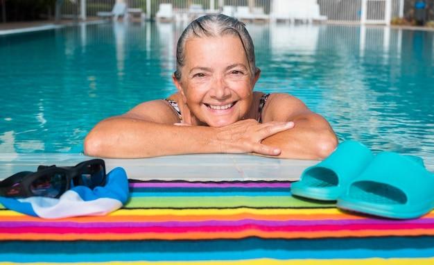 Vieille dame nageant pour rester en forme dans une piscine extérieure avec de l'eau claire et une journée ensoleillée caucasian smiling
