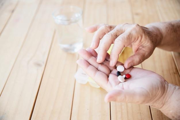 Vieille dame prépare à manger une pilule de médecine quotidienne