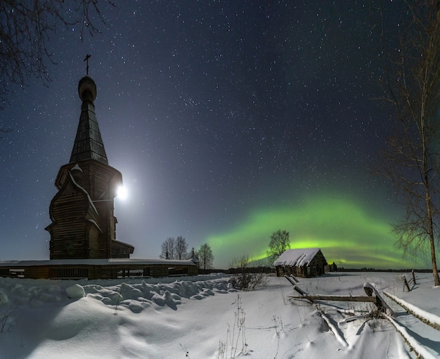 Une vieille église en bois sur le fond des aurores boréales