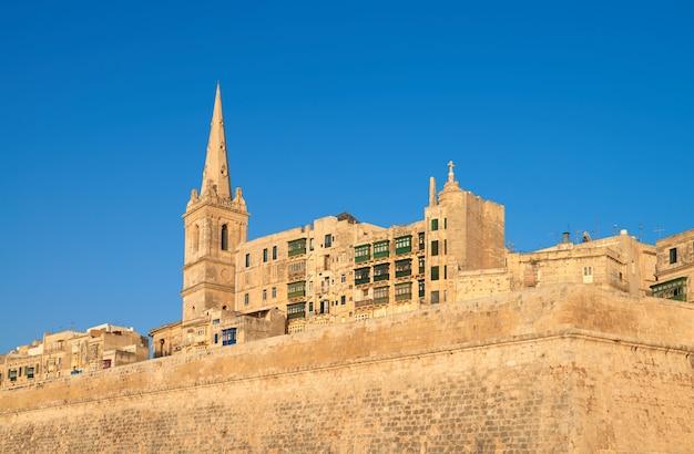 Une vieille église de grès et des maisons à la valette, malte