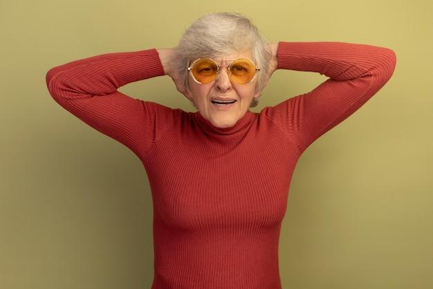 Vieille femme agacée portant un pull à col roulé rouge et des lunettes de soleil regardant droit en gardant les mains derrière la tête isolées sur un mur vert olive