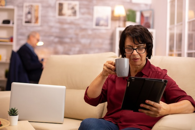 Vieille femme âgée assise sur le canapé et utilisant une tablette numérique dans un salon confortable.