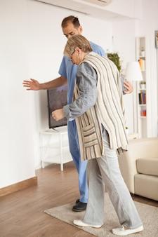Une vieille femme âgée dans une maison de retraite aidée par un médecin de sexe masculin à marcher.