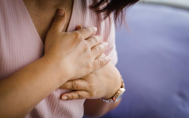 Vieille femme âgée non identifiée assise sur un lit souffrant d'une crise cardiaque soudaine et tenant la poitrine. concept de soins de santé d'urgence et affecté par la réanimation cardio-pulmonaire, problème cardiaque.