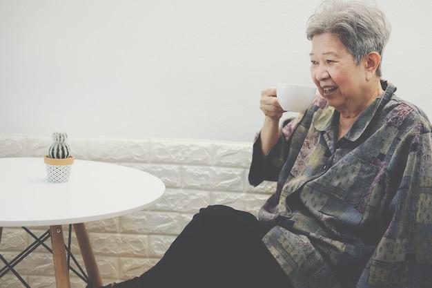 Vieille femme âgée senior senior femme buvant du thé de café moka chaud à la maison.