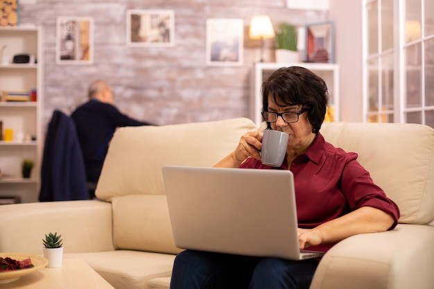 Vieille femme âgée sur son canapé travaillant sur un ordinateur portable moderne dans son salon confortable. son mari est à l'arrière-plan