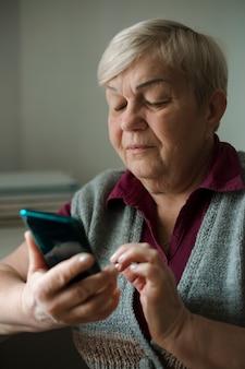 Une vieille femme âgée utilise un téléphone mobile.