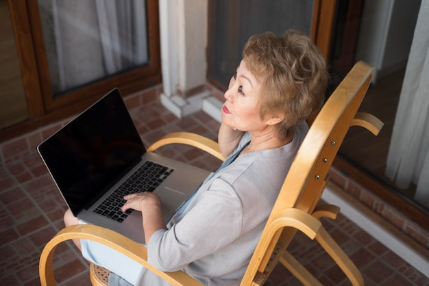 Vieille femme à angle élevé avec ordinateur portable