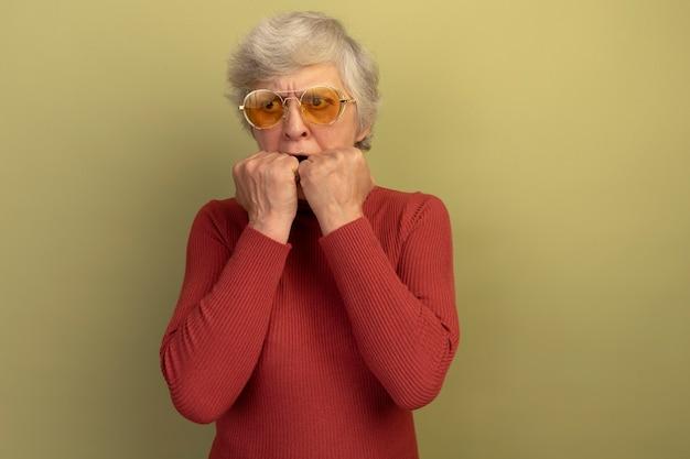 Vieille femme anxieuse portant un pull à col roulé rouge et des lunettes de soleil regardant le côté en gardant les mains sur la bouche isolée sur un mur vert olive avec espace pour copie