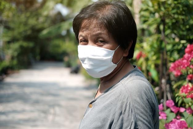 Vieille femme asiatique portant un masque en tissu blanc pour prévenir le virus covid-19 ou corona en thaïlande et la protection contre la pollution atmosphérique pm 2,5