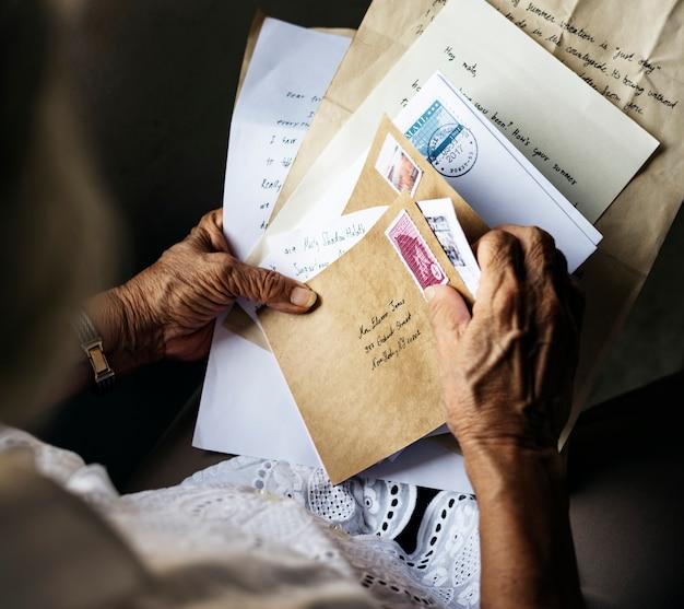 Vieille femme asiatique tenant de vieilles lettres dans ses mains