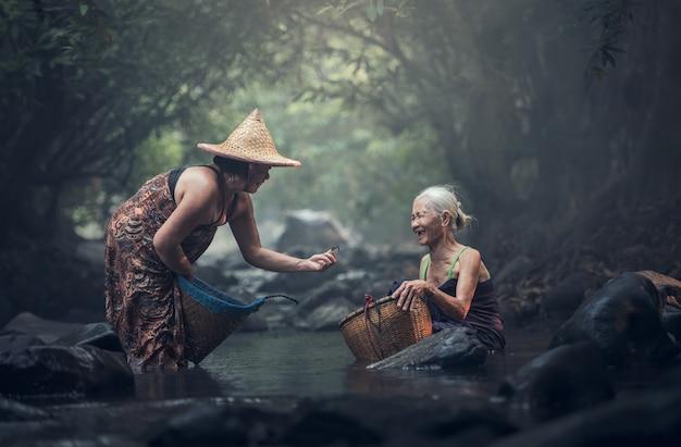 Vieille femme asiatique travaillant dans un ruisseau