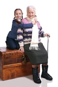 Vieille femme assise sur une boîte avec sa petite-fille