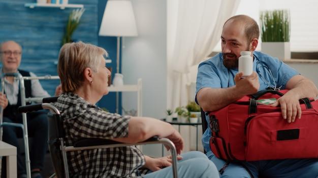 Vieille femme assise en fauteuil roulant recevant une bouteille de pils de l'infirmière homme