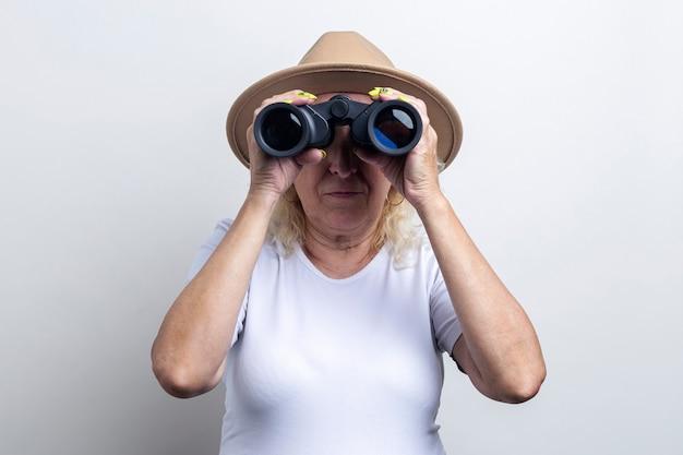 Vieille femme au chapeau regardant à travers des jumelles sur un fond clair.