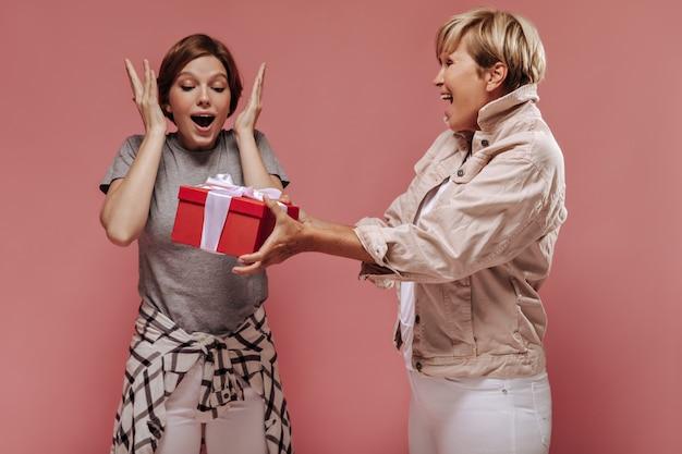Vieille femme aux cheveux blonds en veste donnant une boîte-cadeau rouge à une fille excitante avec une coiffure courte et une chemise à carreaux sur fond rose.
