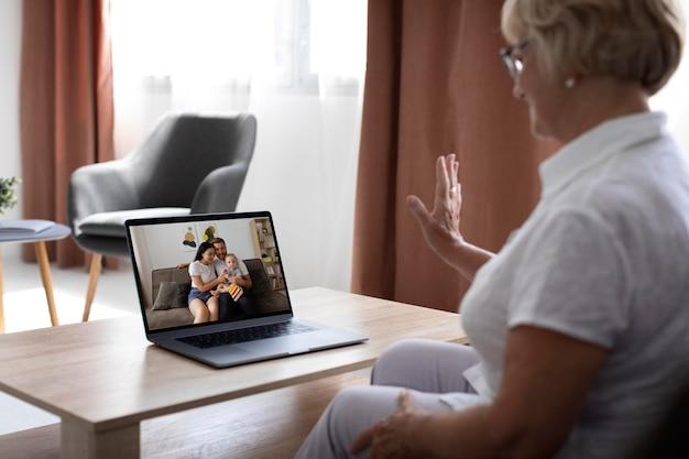 Vieille femme ayant un appel vidéo avec sa famille