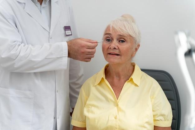 Vieille femme ayant un contrôle de la vue dans une clinique d'ophtalmologie