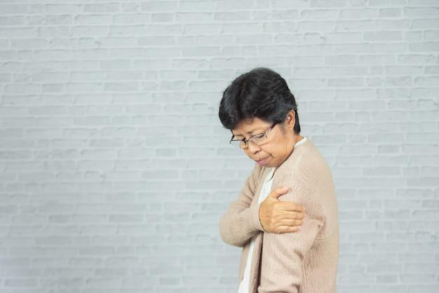 Vieille femme blessée à l'épaule sur gris