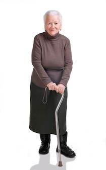 Vieille femme avec une canne qui pose en studio sur fond blanc
