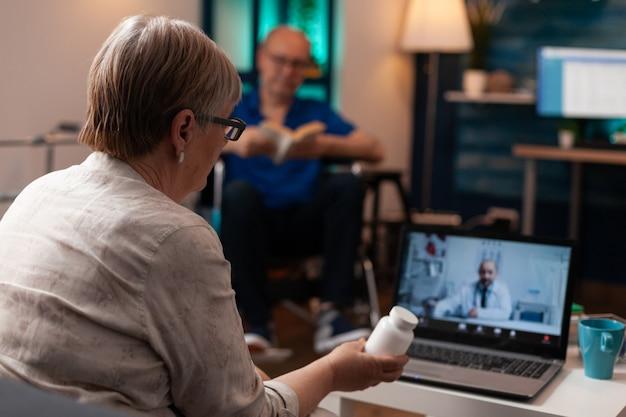 Vieille femme caucasienne utilisant l'appel vidéo de conférence en ligne