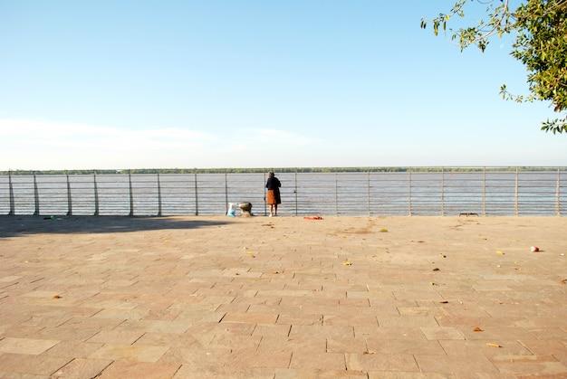 Vieille femme debout devant une rivière. journée ensoleillée.