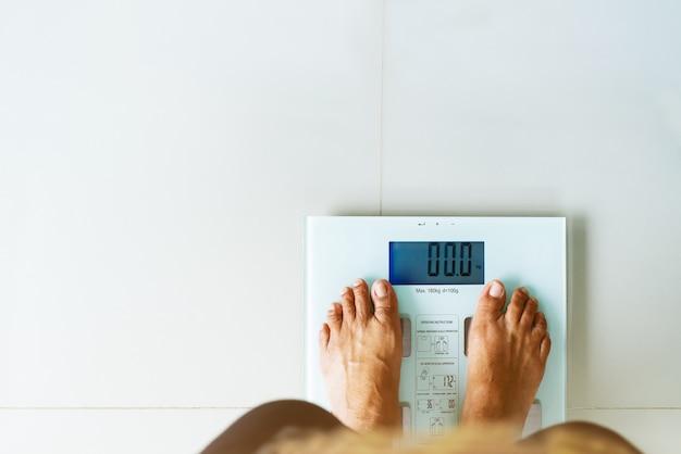 Vieille femme debout sur une échelle de poids de couleur blanche