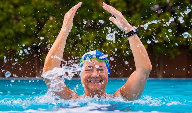 Vieille femme détendue qui aime les activités de piscine sourit en jouant avec de l'eau caché par le jet d'eau