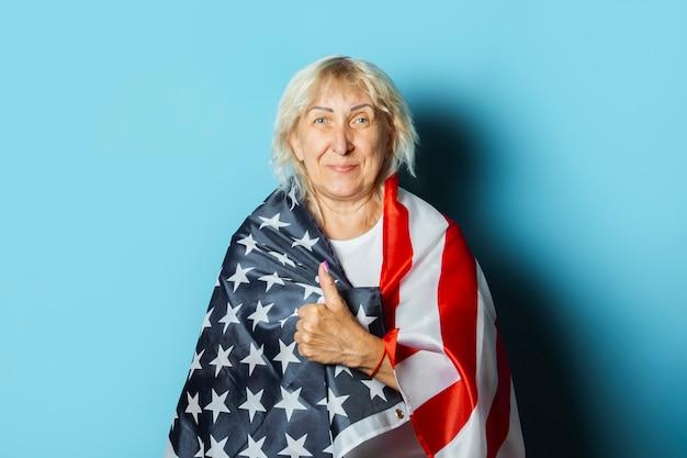 Vieille femme détient le drapeau américain sur fond bleu. concept de célébration de la fête de l'indépendance, jour du souvenir, émigration, drapeau américain