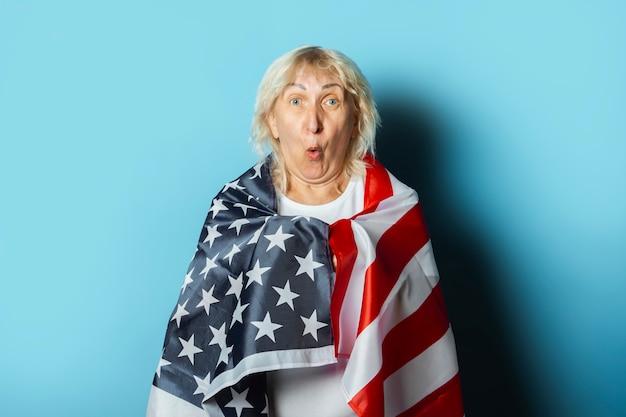 Vieille femme détient le drapeau américain sur fond bleu. concept de célébration de la fête de l'indépendance, jour du souvenir, émigration