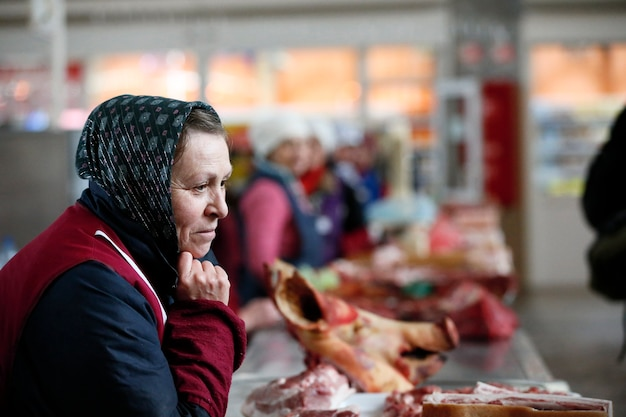 Une vieille femme en écharpe vend du porc.vente de viande. marché de produits carnés