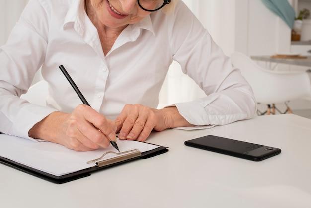 Vieille femme écrivant dans un presse-papiers