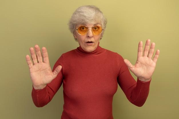 Une vieille femme impressionnée portant un pull à col roulé rouge et des lunettes de soleil regardant l'avant montrant dix mains isolées sur un mur vert olive