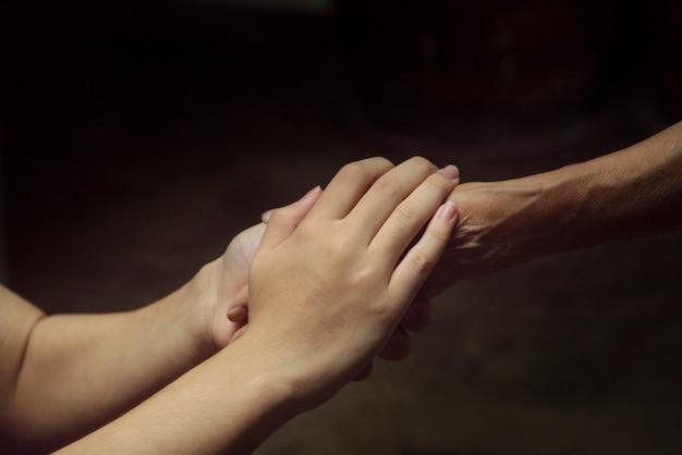 Vieille femme et jeune main dans la main