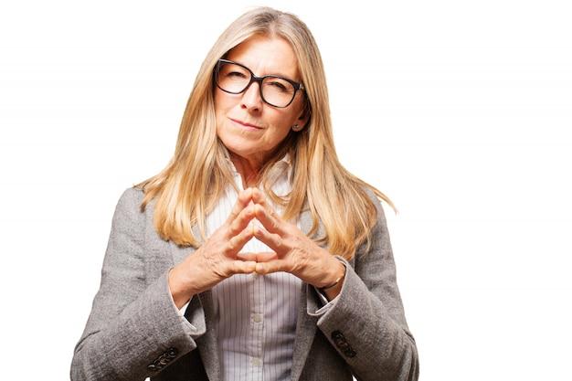 Vieille femme avec des lunettes pour voir et les mains jointes