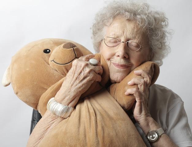 Vieille femme avec des lunettes serrant un ours en peluche