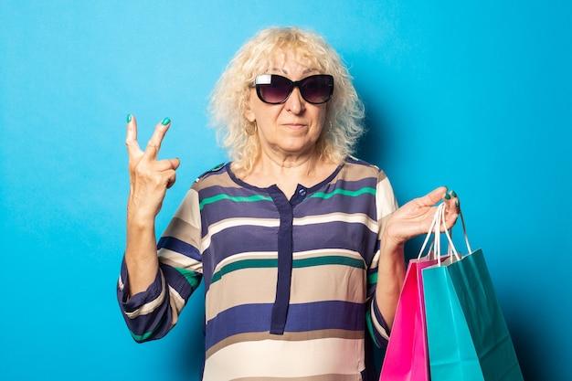 Vieille femme avec des lunettes tient des sacs à provisions et montre un geste amical et bienvenu sur le mur bleu.