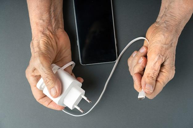 Vieille femme mains froissées tenant un chargeur pour smartphone.