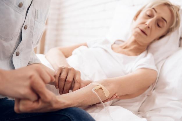 Une vieille femme malade s'allonge sur le lit et ressent une douleur.