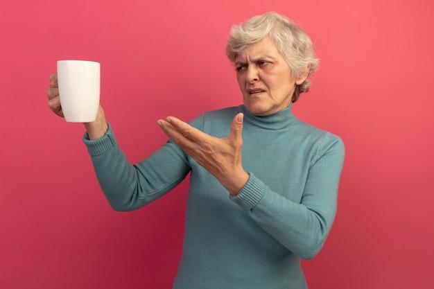 Une vieille femme mécontente portant un pull à col roulé bleu tenant regardant et pointant avec la main une tasse de thé