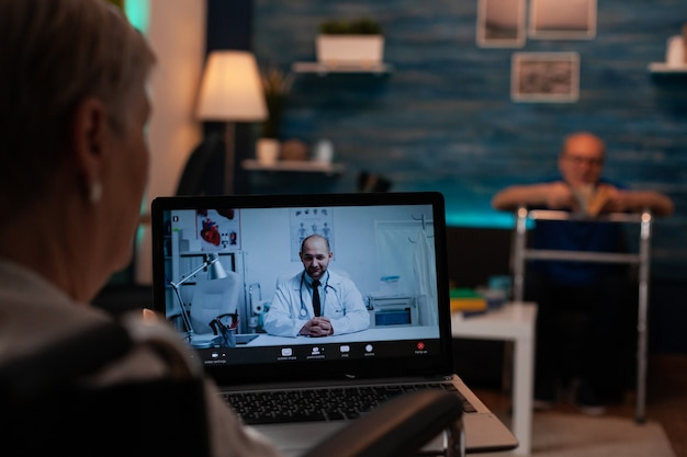 Vieille femme parlant au docteur sur la conférence d'appel vidéo