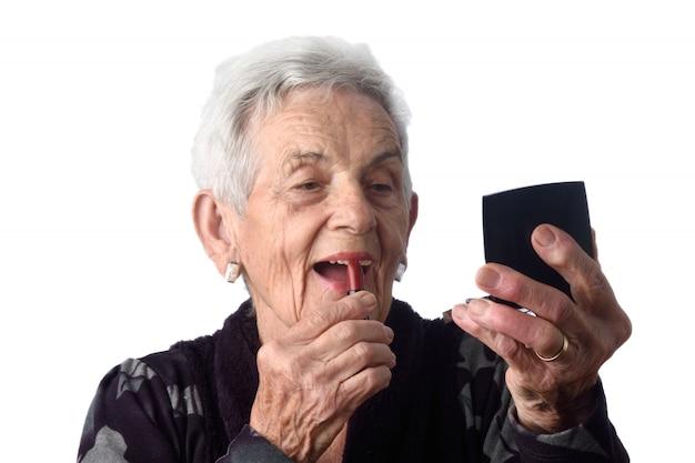Vieille femme peignant ses lèvres sur fond blanc
