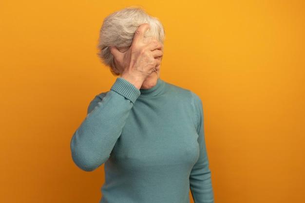 Vieille femme portant un pull à col roulé bleu mettant la main sur le visage isolé sur un mur orange avec espace pour copie