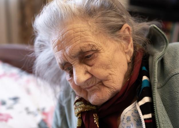 Vieille femme. portrait de très vieille femme fatiguée dans la dépression assis à l'intérieur sur le lit