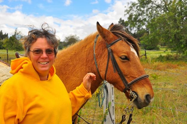 Vieille femme posant avec son cheval