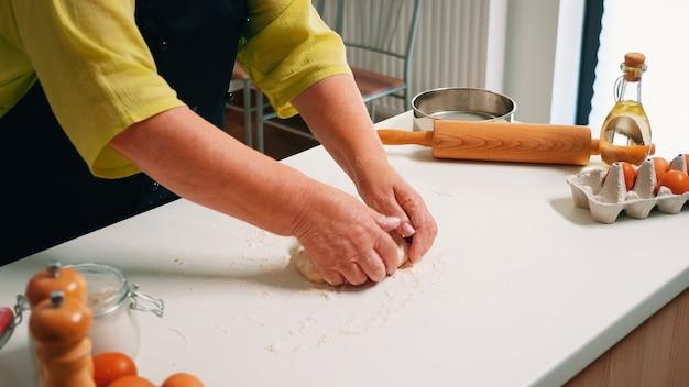 Vieille femme préparant la pâte à pâtisserie sur table en bois dans la cuisine à domicile. chef âgé à la retraite avec saupoudrage uniforme, tamisage, tamisage des ingrédients bruts et mélange de farine pour la cuisson de pizzas maison, de pain.
