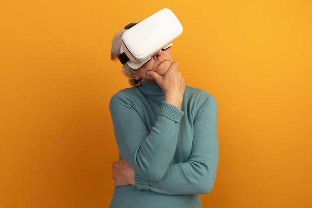 Une vieille femme réfléchie portant un pull à col roulé bleu et un casque vr mettant la main sur le menton isolé sur un mur orange avec espace pour copie