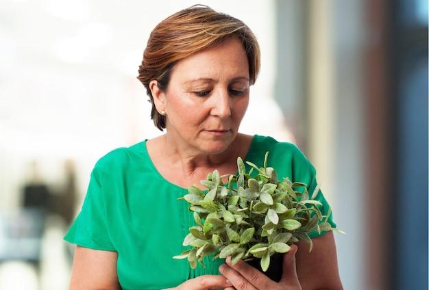 Vieille femme regardant une plante